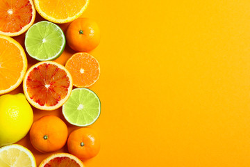 Fototapete - Different citrus fruits on color background, flat lay. Space for text