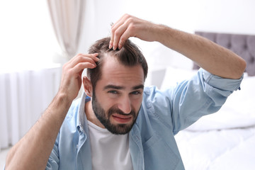 Young man with hair loss problem indoors Wall mural