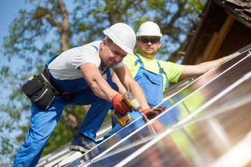 Two professional technicians installing solar photo voltaic panel to metal platform using screwdriver. Stand-alone solar system installation, alternative renewable energy generation concept.