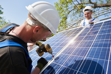 Technician connecting solar photo voltaic panel to metal platform using screwdriver on bright blue sky and shiny panel surface background. Stand-alone solar panel system installation concept.