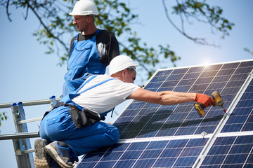 Two workers mounting heavy solar photo voltaic panel on tall steel platform using screwdriver on blue sky background. Exterior stand-alone solar panel system installation, dangerous job concept.