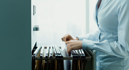 Fototapeta Office clerk searching files in the filing cabinet