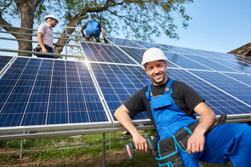 Portrait of smiling technician with electrical screwdriver in front of unfinished high exterior solar panel photo voltaic system with team of workers on high platform.
