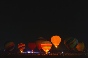 Hot Air Balloons At Night On Balloon Festival. Balloon Festival in Kazakhstan. Show night glow at the festival balloons. Flying on aerostats in the evening.