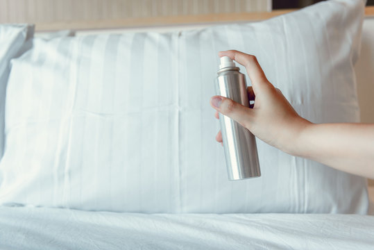 Woman Hand is Spraying Air Freshener into Pillow on Bedroom, Close-Up of Woman Hand is Holding Bottle of Air-Freshener Spray Container While Application into a Pillow Fabric. Home Hygienic and Care