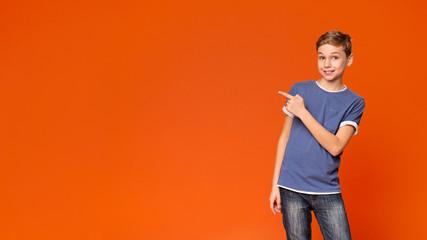 Cute little boy pointing away on orange background