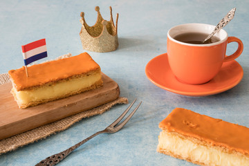 Orange tompouce, traditional Dutch treat with pudding and frosting on national holiday Kings Day (April 27th), in The Netherlands. With cup of tea, crown and Dutch flag