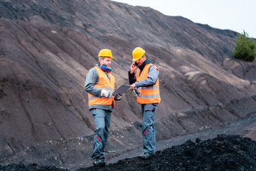 Workers in open-cast mining operation pit