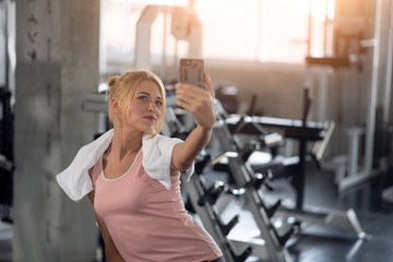 Young sportive woman taking selfie with mobile phone in gym