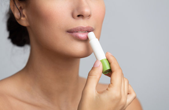 Lips nutrition. Girl applying hygienic balm over grey background