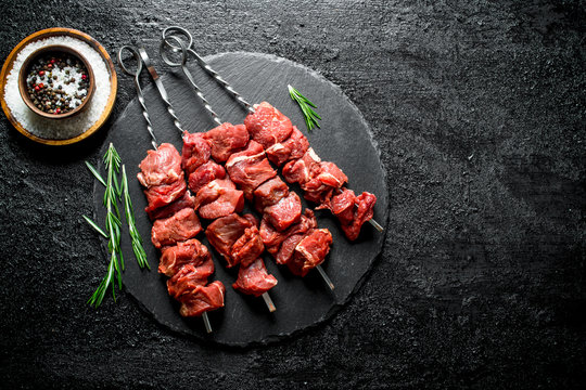Raw kebab on a stone Board with rosemary and spices.