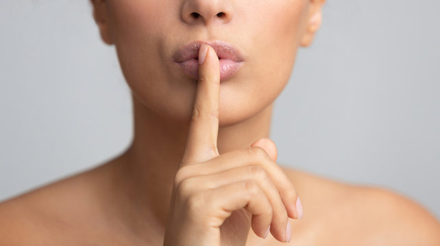Silent gesture. Woman holding finger on lips