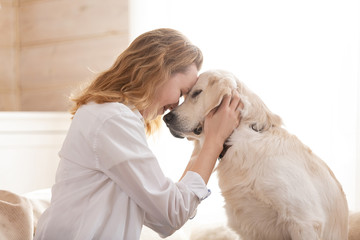Fototapeta Young pretty woman in casual clothes hugging her beloved big white dog sitting on the sofa in the living room of her cozy country house. Animal communication concept obraz