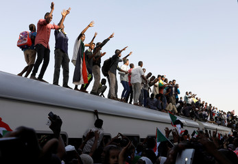 Protesters on a train from Atbara, the birthplace of an uprising that toppled Sudan's former President Omar al-Bashir, shout slogans as they approach to a train station in Khartoum