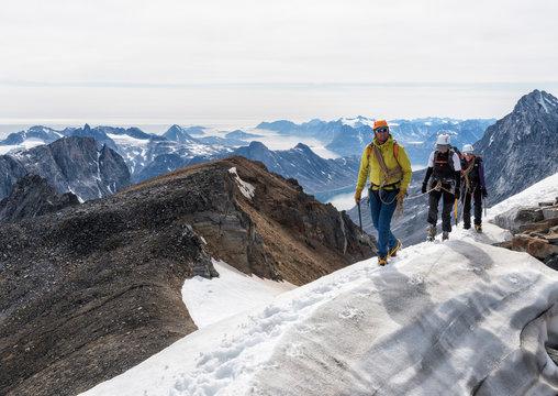 Greenland, Sermersooq, Kulusuk, Schweizerland Alps, mountaineers walking in snowy mountainscape