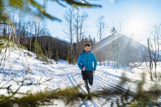 Germany, Bavaria, sportive man running in winter