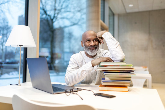 Portrait of smiling mature man sitting at desk with laptop and stack of books