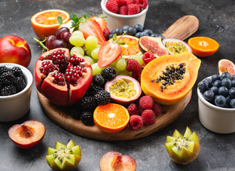 Wall Mural - Delicious fruit platter pomegranate papaya oranges passion fruits berries on wooden board on dark concrete background, selective focus, copy space