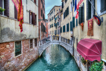 Bridge and flags on a canal in Venice, Italy