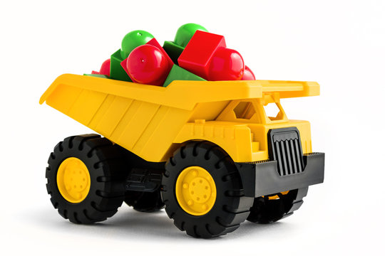 yellow dump truck toy with colorful plastic blocks on white background