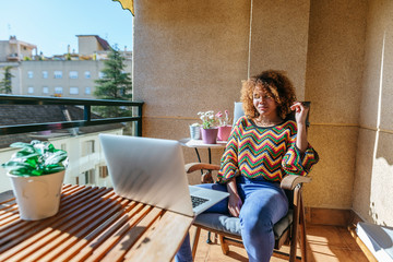 Young woman with curly hair sitting on balcony using laptop