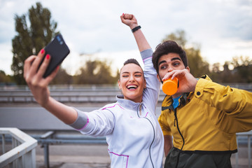 Active sport couple make fun and take selfie after run outdoor