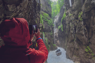 Germany, Bavaria, Partnach Gorge near Garmisch-Partenkirchen, man with red rain jacket taking a photo with smarthone