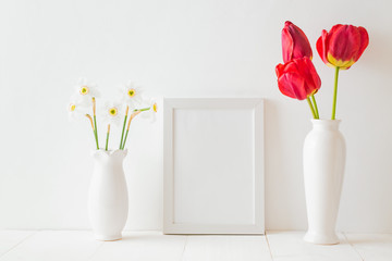 Mockup with a white frame and red tulips in a vase on a white wooden table