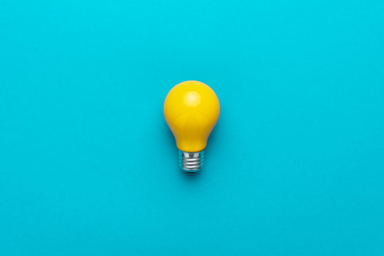 flat lay minimalist photo of yellow painted bulb on turquoise blue backgound
