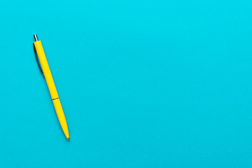photo of yellow ballpoint pen over turquoise blue background with copy space