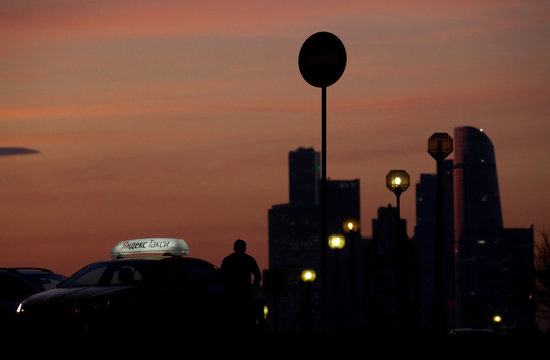 A driver rests next to a car with Yandex Taxi logo on the roof during sunset in Moscow