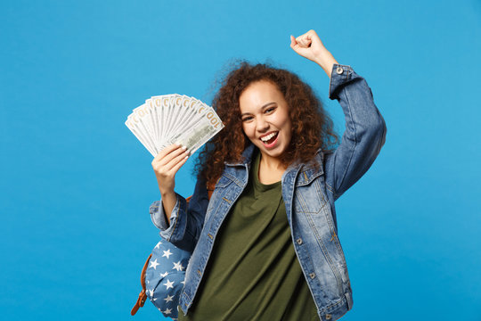 Young african american girl teen student in denim clothes, backpack hold cash money isolated on blue background studio portrait. Education in high school university college concept. Mock up copy space