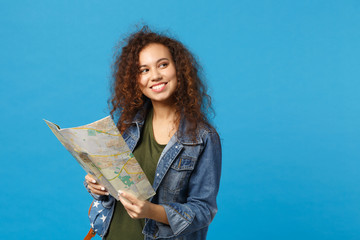 Young african american girl teen student in denim clothes, backpack hold map isolated on blue wall...