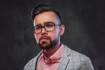 Portrait of sceptical proud man in checkered  blazer, pink shirt and glasses.