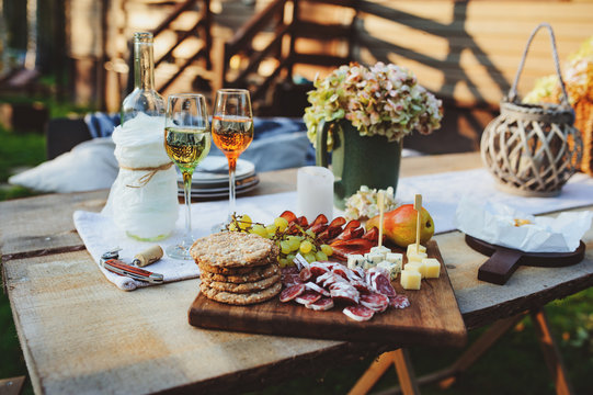 wine, cheese, ham and fruits served on wooden cutting board. Summer outdoor garden party