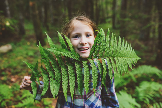 kid girl exploring summer forest, playing with wild ferns. Teaching kids to love nature, summer camping concept