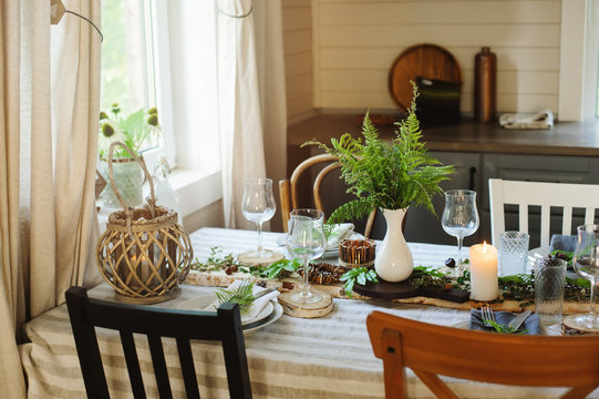 rustic country kitchen interior with festive table setting for summer dinner in natural green and brown tones. Small wooden cottage.