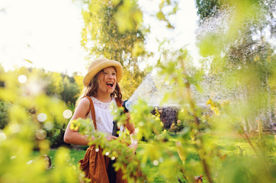 happy child girl watering flowers with hose in summer garden, holding water sprinkler, playing outdoor