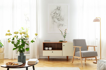 White roses in vase, cookies on the plate and books on wooden coffee table in fashionable living room with wooden cabinet and retro armchair
