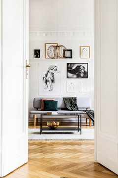 Vertical view of open door to sophisticated living room interior with grey sofa, industrial coffee table and golden chandelier