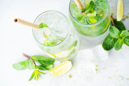 Top view of two glasses with tropical mojito cocktail on light background with copy space. Summer time vacation concept.Flat lay.