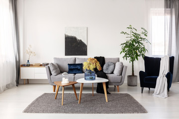 Flowers in blue glass vase and two white candles on wooden coffee tables in grey elegant living room with comfortable sofa