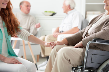 Close-up on friendly nurse holding hand of smiling senior person in the wheelchair