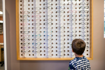Young boy looking at glasses selection in eye doctor office
