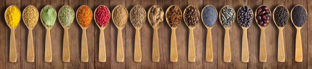 Fototapete - Colorful spices on background wooden table. Seasonings and herbs in wooden spoons for design website headers.