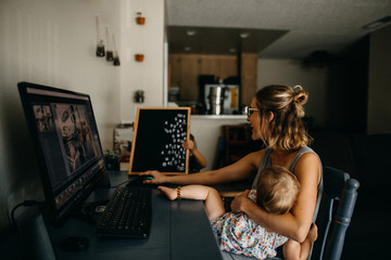 Woman holding her daughter while working on laptop at home