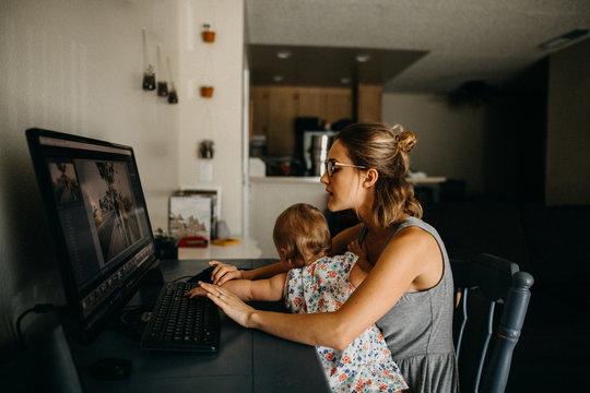 Multitasking working mother holding baby and typing on computer