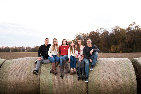 Wide View of Big Happy Family Sitting on  Hay Bales in Field at Sunset