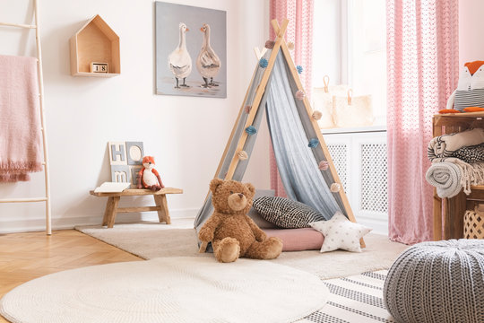 Teddy bear and star pillow in front of tent in child's room interior with pouf and poster. Real photo