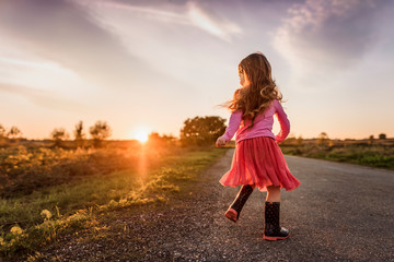 girl plays in evening sun twirling on road with backlight